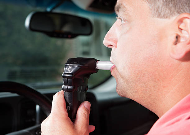 Driver Blowing into Vehicle Alcohol Ignition Interlock System stock photo