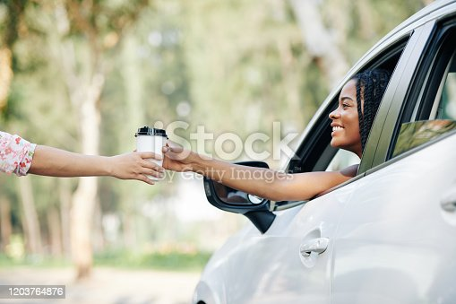 Happy pretty young Black woman buying coffee in drive through coffeeshop
