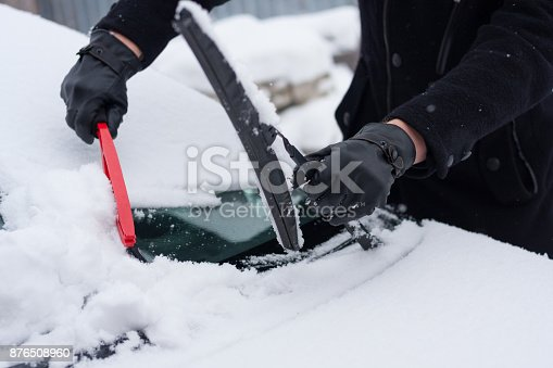 istock Driver clean his car after snowfall 876508960