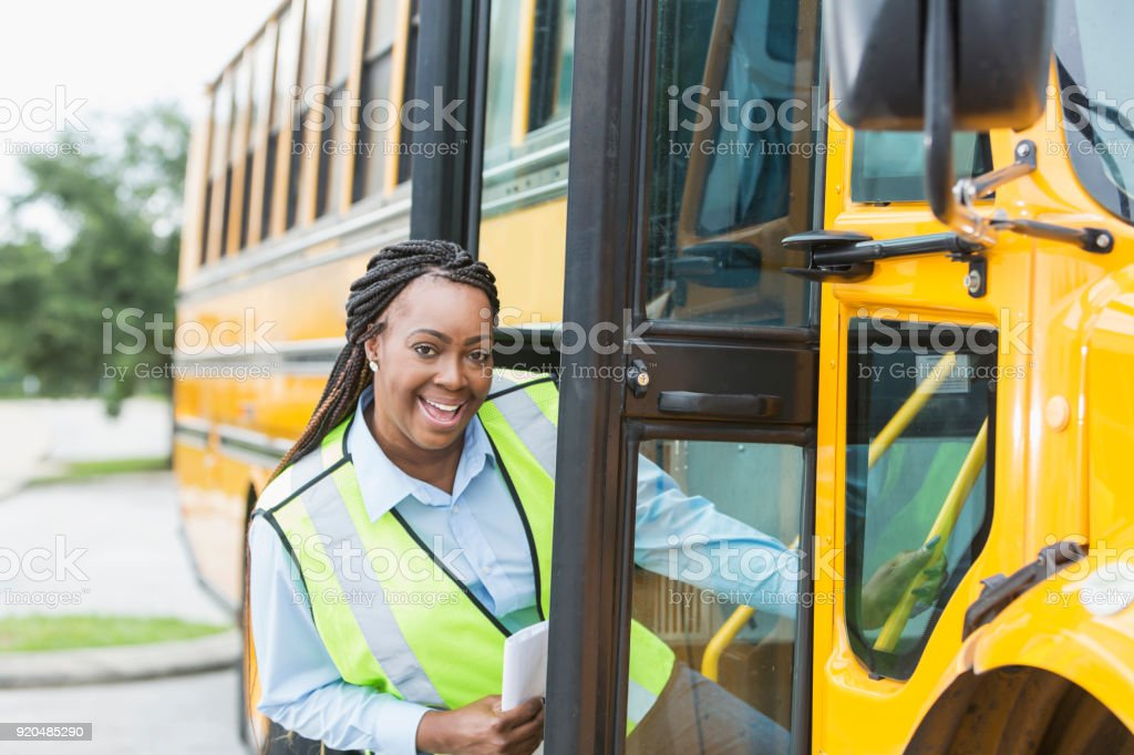 Driver climbing onto school bus stock photo