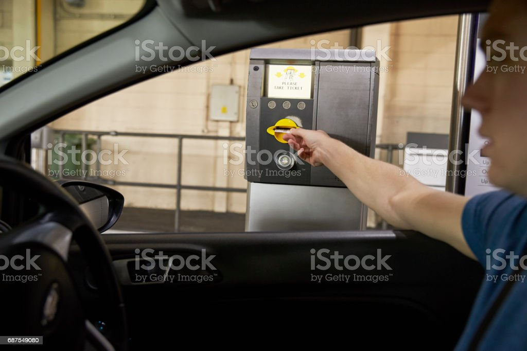 Driver Collects Ticket From Machine In Car Park stock photo