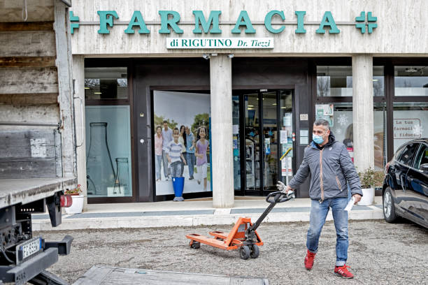 A driver consigns the last PPF3, N95 masks to the chemist in Rigutino, Province of Arezzo Italy. AREZZO, ITALY - MARCH 26, 2020: A driver consigns the last PPF3, N95 masks to the chemist in Rigutino, Province of Arezzo Italy. arezzo stock pictures, royalty-free photos & images