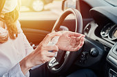 istock Driver disinfection hands with antibacterial sanitizer in the car before driving. Coronavirus preventative measure 1221166587