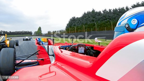 Racing driver driving red Formula car on track.