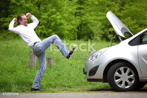 istock Driver furious a broken car by the road 472207316
