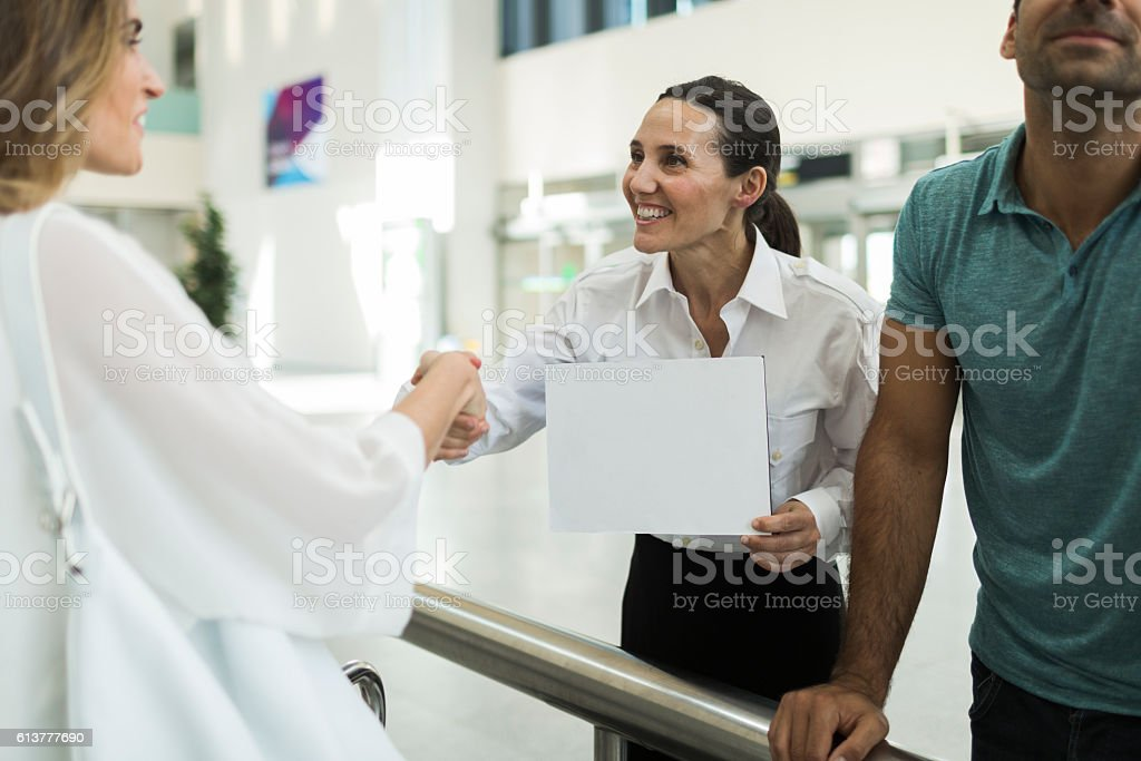 Driver greeting business woman with a sign on arrival terminal. stock photo