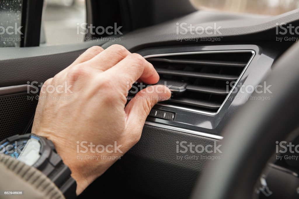 Driver hand on air ventilation grille stock photo