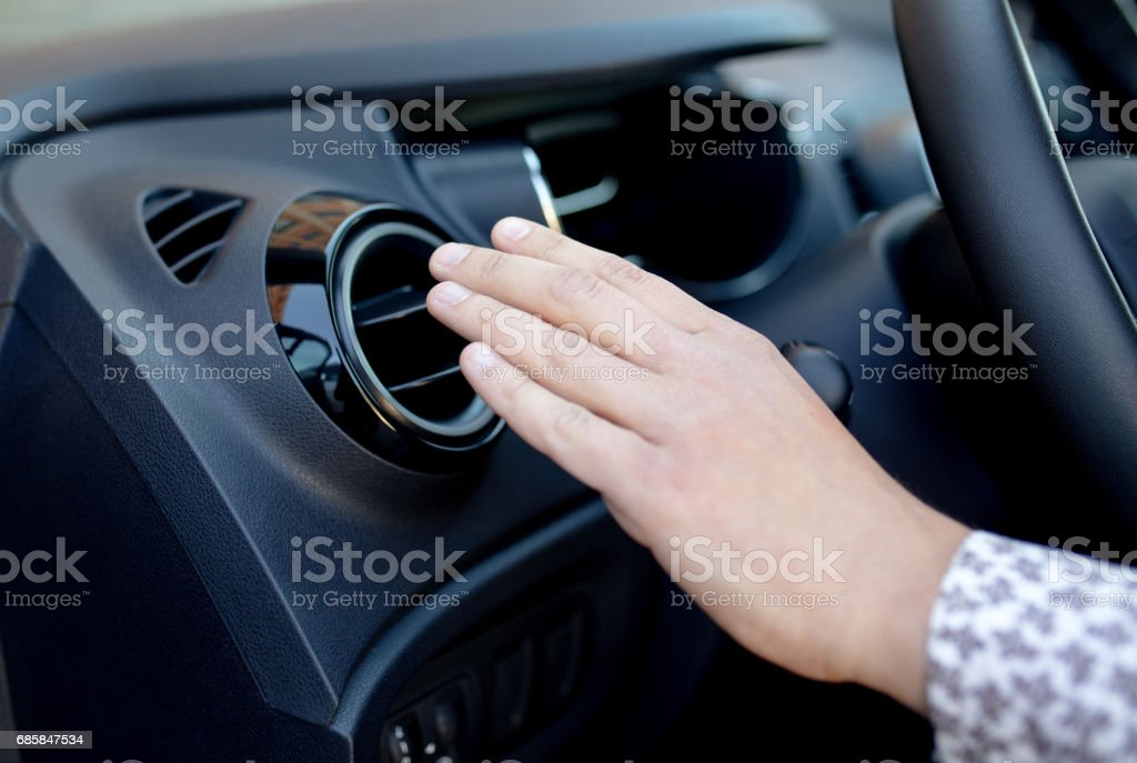 Driver hand on air ventilation grille with power regulator, modern car interior detail stock photo