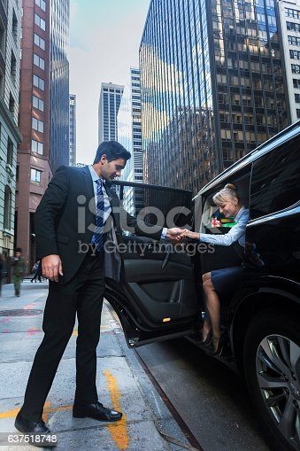 Young male driver helping a happy female passanger getting our of luxury black car in New York City