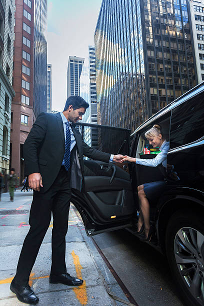 driver helping passanger out of luxury car - limousine service stock photos and pictures