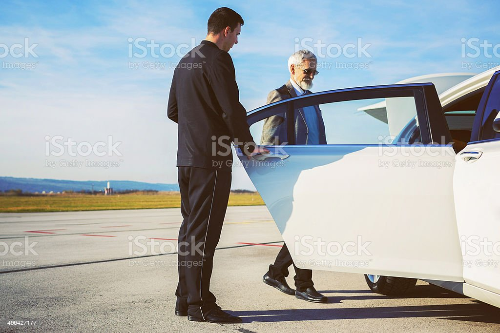 Driver helping senior adult into limousine at airport stock photo