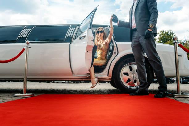 Fahrer hilft VIP Frau oder Stern aus Limo auf roten Teppich – Foto