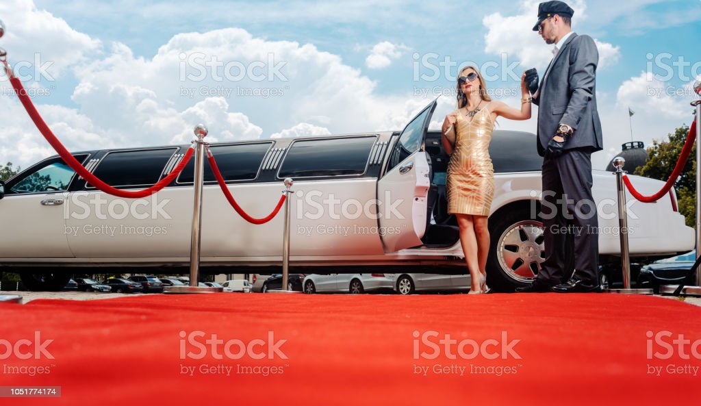 Driver helping VIP woman or star out of limo on red carpet stock photo