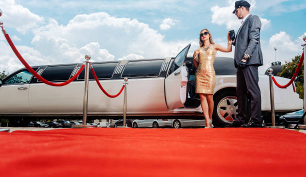 Driver helping VIP woman or star out of limo on red carpet Driver helping VIP woman or star out of limo on red carpet to a reception first class stock pictures, royalty-free photos & images