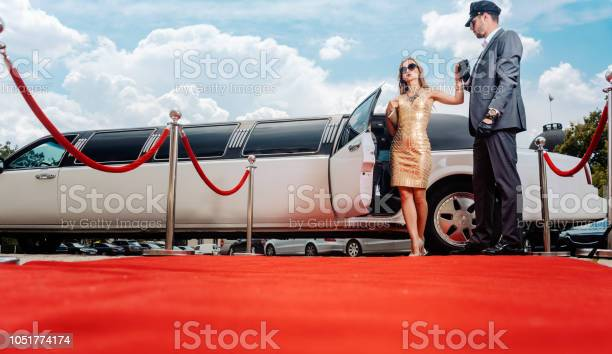 Photo of Driver helping VIP woman or star out of limo on red carpet