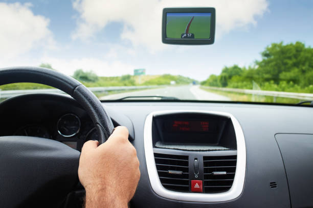 Driver holding steering wheel while using gps navigation system stock photo