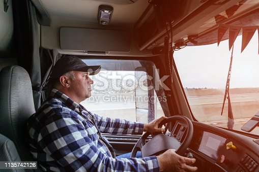 istock Driver in cabin of big modern truck 1135742126