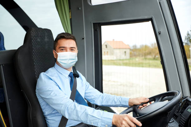 driver in medical mask driving intercity bus stock photo