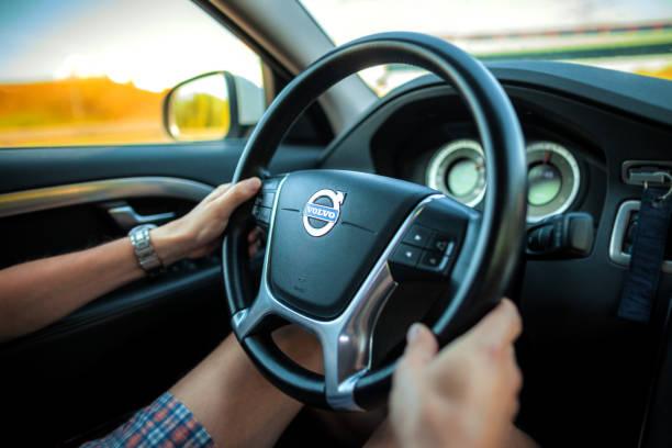 föraren i shorts innehar en volvo ratten under bil rida på motorvägen. - volvo bildbanksfoton och bilder