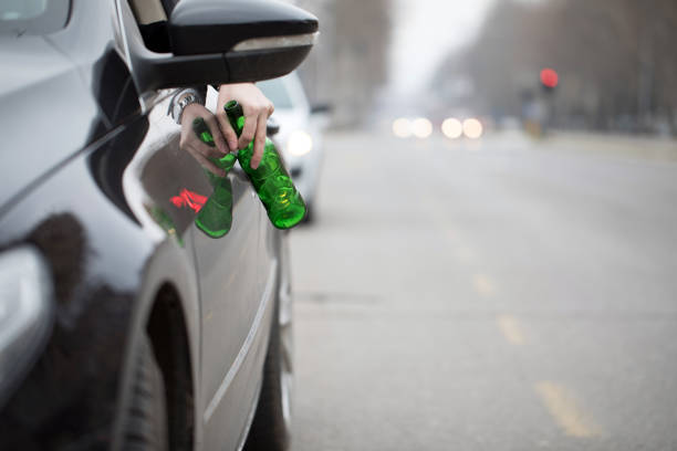 Driver in the car drinks beer stock photo