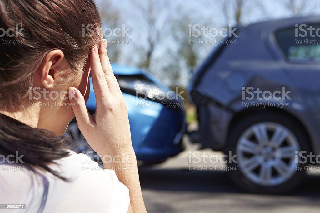Driver looking at damaged cars after accident stock photo
