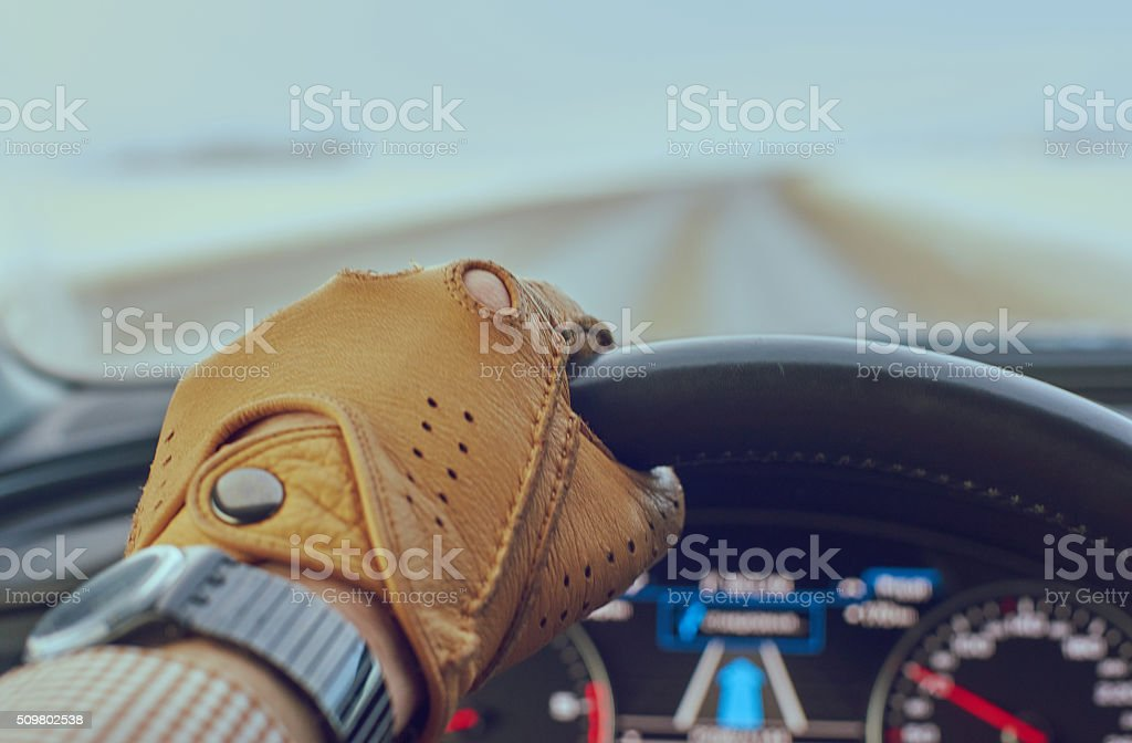 Driver man hand in glove on steering wheel stock photo