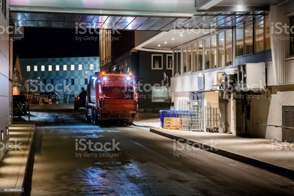 Driver of garbage collecting truck prepares garbage container for loading. stock photo