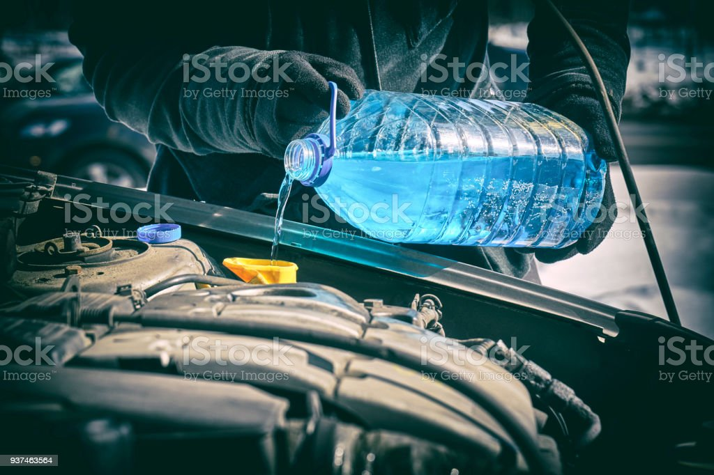 Driver pouring an antifreeze liquid in a windshield washer tank of a car stock photo