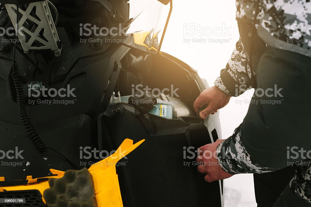 Driver repairing a broken snowmobile. Winter sports. royalty-free stock photo