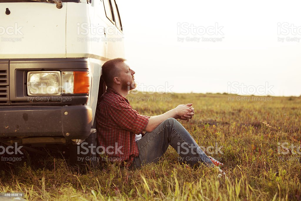 Driver resting in a field near his car stock photo