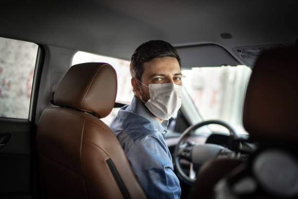 Driver taking to a passenger on seat back wearing protective medical mask stock photo