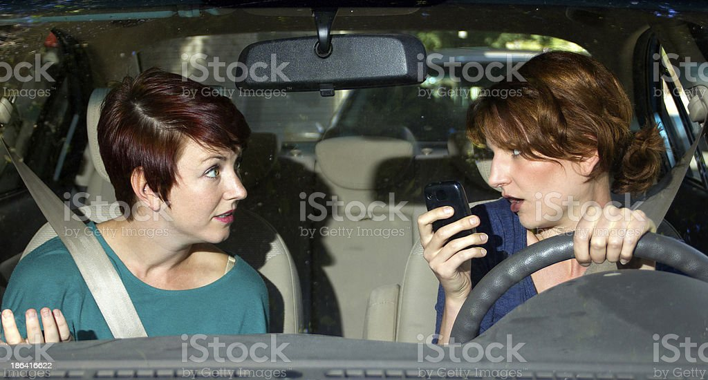 Driver Texting And Driving in a Car with a Passenger royalty-free stock photo