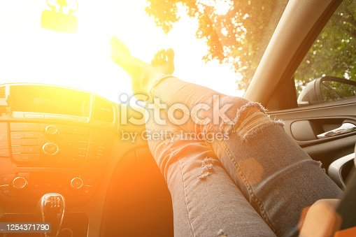 Driver training car on road in summer sunny day. Happy young woman inside vehicle driving. Vacation ride trip travel concept