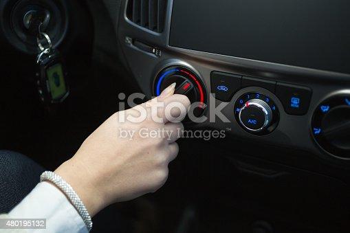 istock driver turning car air conditioner knob 480195132