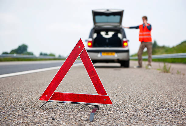A driver uses a warning triangle while pulled over stock photo