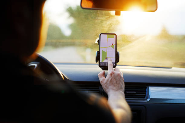 Driver uses navigation on his mobile phone in the car Driver uses navigation on his mobile phone in the car global positioning system stock pictures, royalty-free photos & images