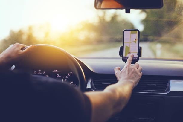 conductor que utiliza la navegación gps en el teléfono móvil mientras conduce el coche - conducir fotografías e imágenes de stock