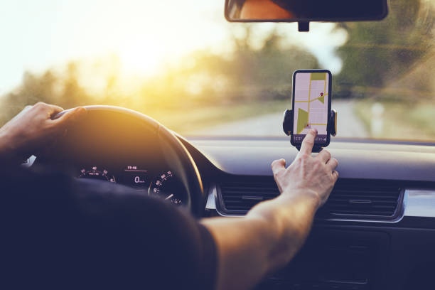 Driver using GPS navigation in mobile phone while driving car stock photo