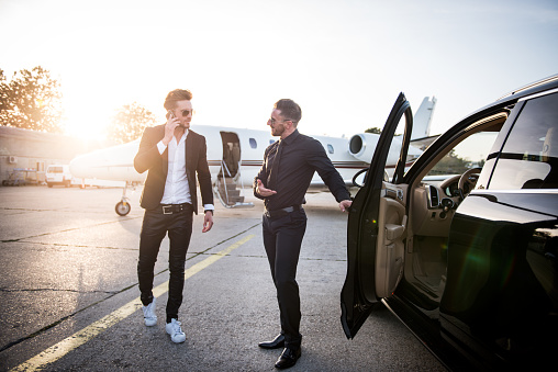Young man with sunglasses dressed in black standing next to car and opening door to celebity that just arrived by private jet airplane seen in the background. He is also talking over mobile phone.