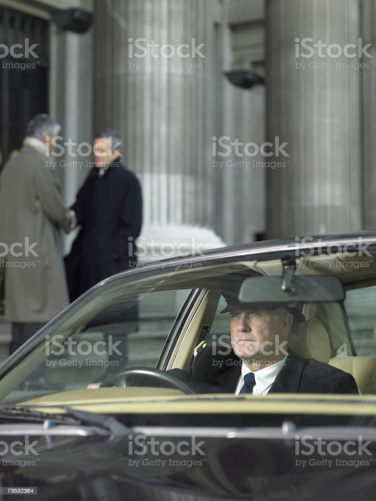 Driver waiting in car for men shaking hands on steps in background royalty-free stock photo