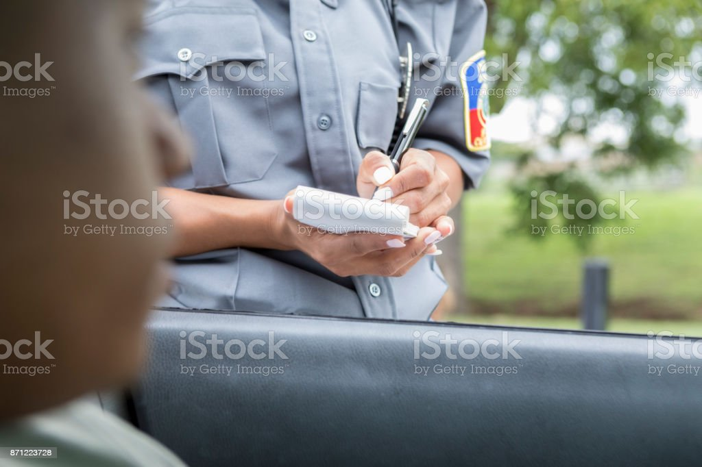 Driver waits as police officer writes speeding ticket - foto stock