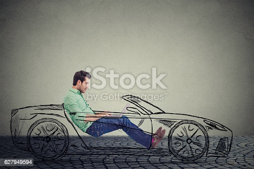 Driverless self driving car technology concept. Side profile young handsome man using laptop computer while driving a car