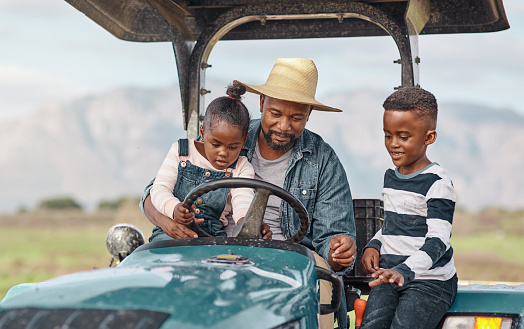 Shot of a mature man driving a tractor with his adorable son and daughter on a farm