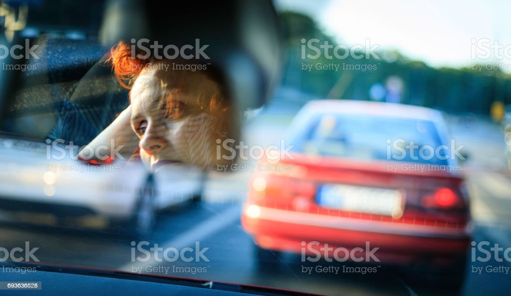 driver's face in a car mirror stock photo