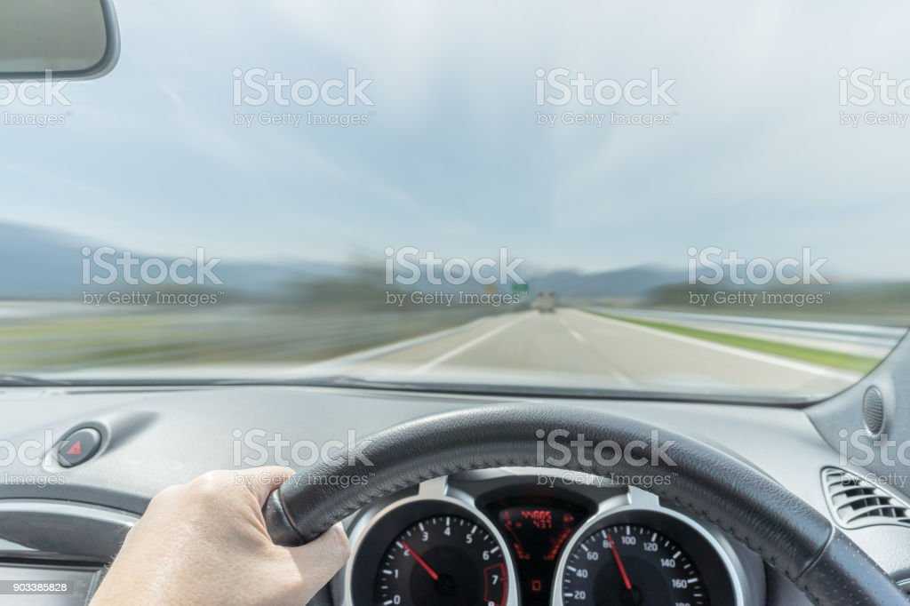 Driver's perspective in a car driving on to a scenic road. Motion blurred the view as if the driver is driving the car very fast stock photo