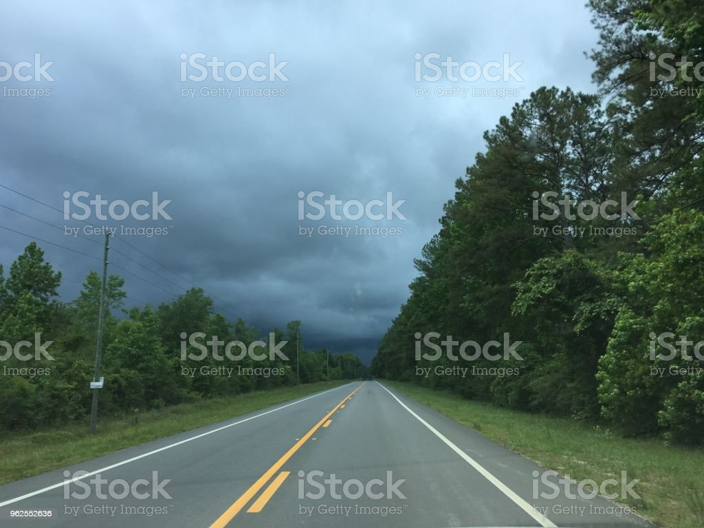 Driver's view down long paved road into dark storm - Royalty-free Cloud - Sky Stock Photo