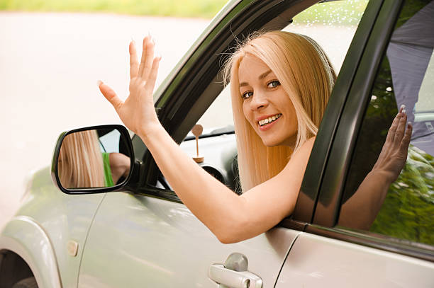 Driver-woman of car waves back stock photo