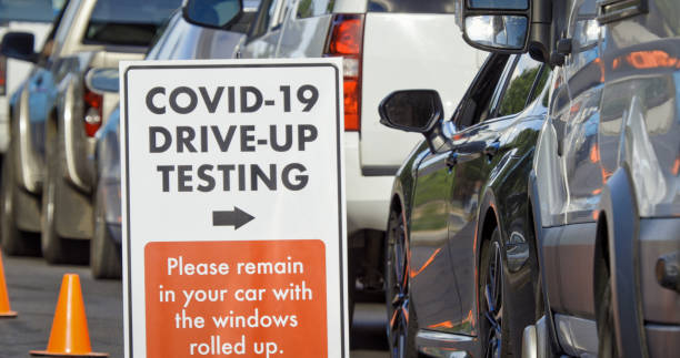 """A """"COVID-19 Drive-Up Testing"""" Sign Sits in the Foreground While Cars and Other Vehicles Wait in a Drive-Up (Drive Through) COVID-19 (Coronavirus) Testing Line Outside a Medical Clinic/Hospital Outdoors (Second Wave) in the Background A """"COVID-19 Drive-Up Testing"""" Sign Sits in the Foreground While Two Female Nurses Wearing Gowns and Surgical Face Masks Talk to Patients in their Cars in a Drive-Up (Drive Through) COVID-19 (Coronavirus) Testing Line Outside a Medical Clinic/Hospital Outdoors (Second Wave) in the Background medical test stock pictures, royalty-free photos & images"""