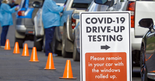 """A """"COVID-19 Drive-Up Testing"""" Sign Sits in the Foreground While Two Female Nurses Wearing Gowns and Surgical Face Masks Talk to Patients in their Cars in a Drive-Up (Drive Through) COVID-19 (Coronavirus) Testing Line Outside a Medical Clinic/Hospital Outd A """"COVID-19 Drive-Up Testing"""" Sign Sits in the Foreground While Two Female Nurses Wearing Gowns and Surgical Face Masks Talk to Patients in their Cars in a Drive-Up (Drive Through) COVID-19 (Coronavirus) Testing Line Outside a Medical Clinic/Hospital Outdoors (Second Wave) in the Background medical test stock pictures, royalty-free photos & images"""
