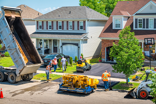 Workers work during driveway paving in front of a house in Brantford Ontario Canada.